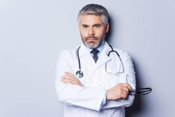 Confident doctor. Mature grey hair doctor looking at camera and keeping arms crossed while standing against grey background