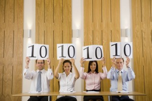 """Four business people holding up score cards with """"10"""" on them"""