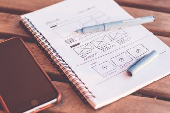 An image showing a UX Designer's notepad with some hand-drawn wireframes